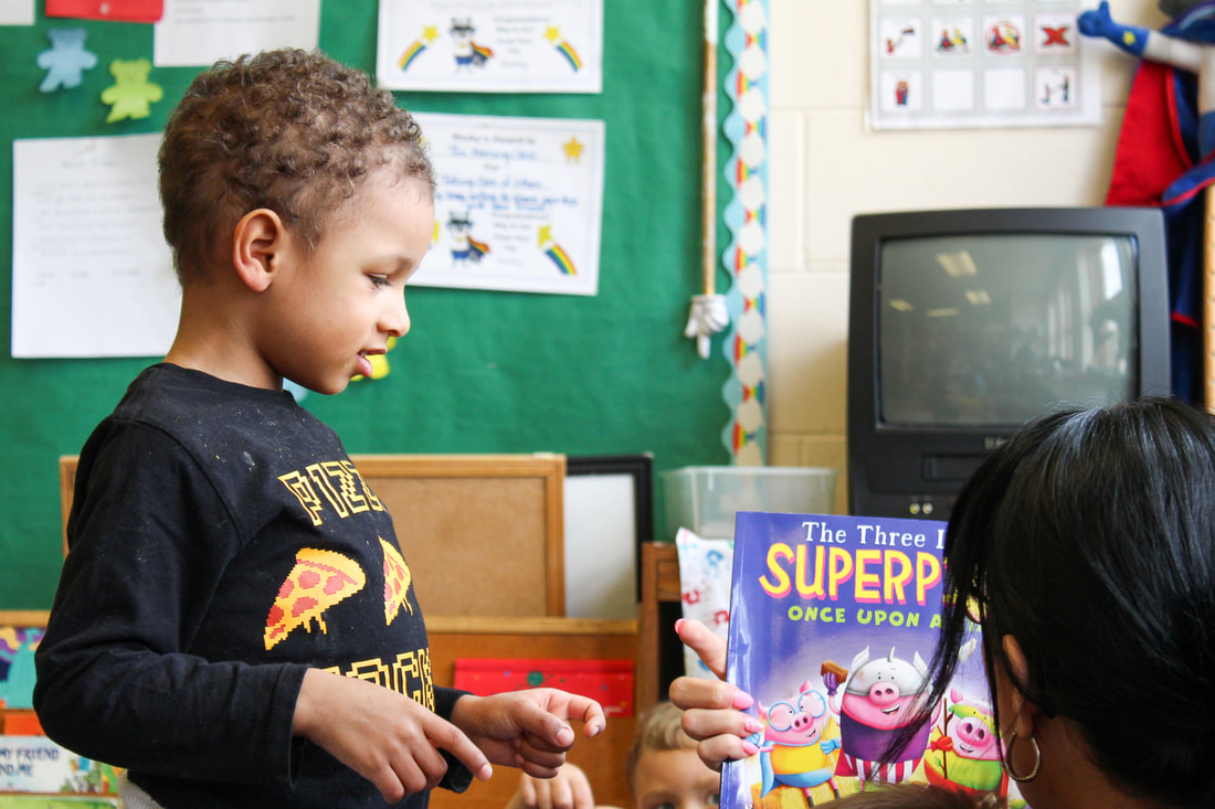 student at RCC reading a book with his teacher